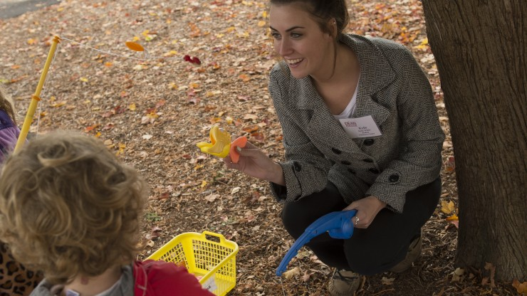 A student crouches while holding up toys to engage three children standing around her outside of the Children's Center.