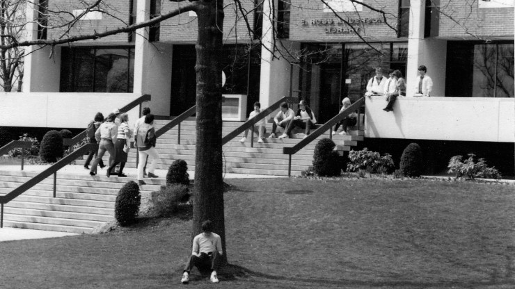 Students sitting outside of the library at Dean College.