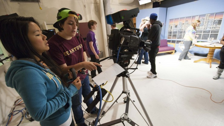 Students working behind the camera reviewing a script on the set of a television show.