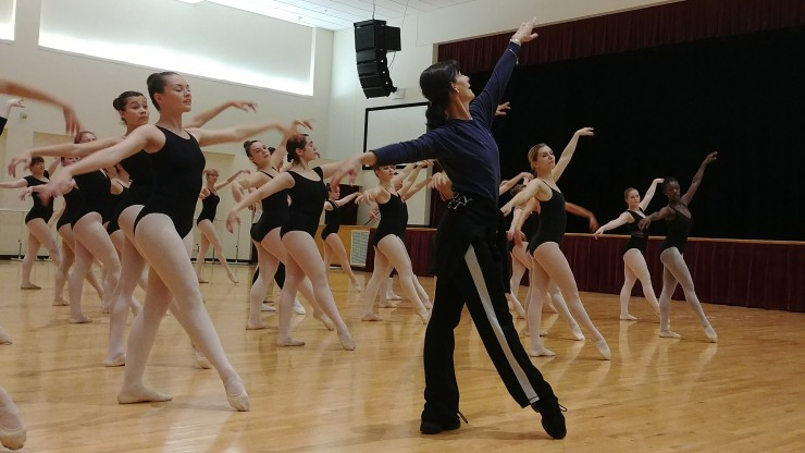 A dance professor leading students through dance during class while the group follows along.