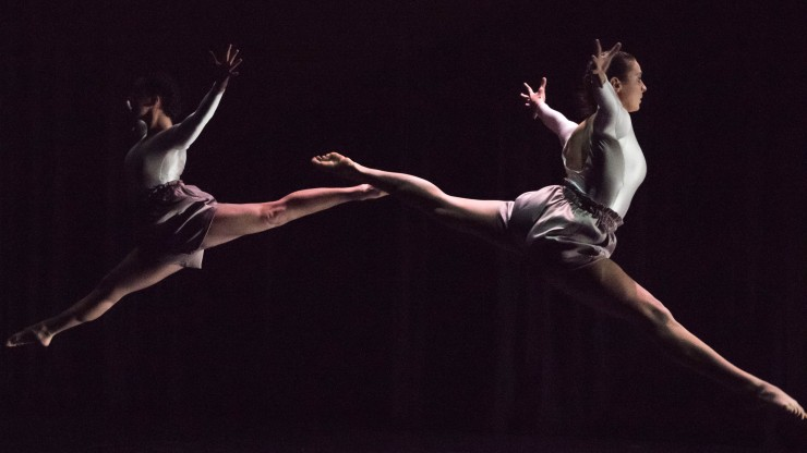 Two dancers jump with legs out during a dance performance.