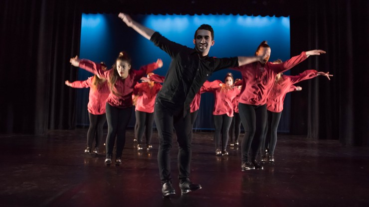 A group of students dancing with arms out during a tap dance performance.