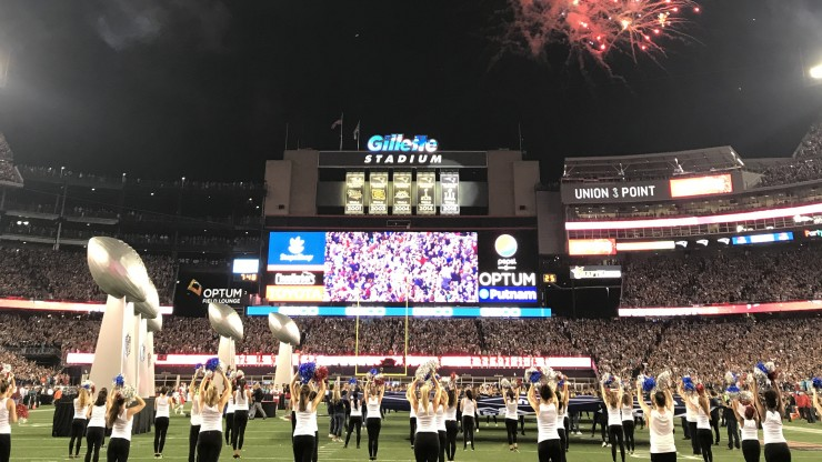 Dean College students dancing on the field at Gillette Stadium during a performance at a New England Patriots game.