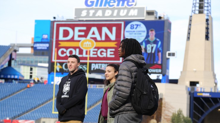 Three students standing on the football field at Gillette Stadium, home of the New England Patriots.