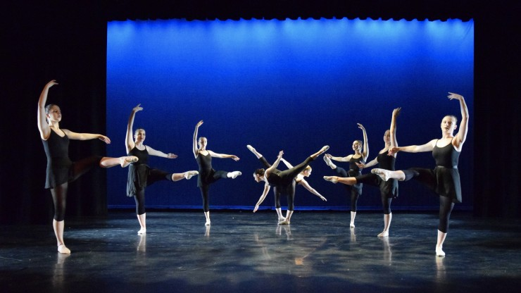 Eight dance students performing ballet during a performance onstage.