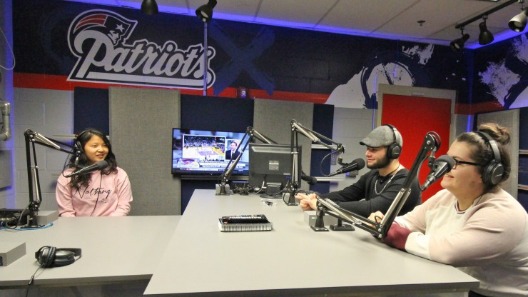 Three students inside the Patriots radio broadcasting studio, receiving hands-on experience at the radio broadcasting microphone.