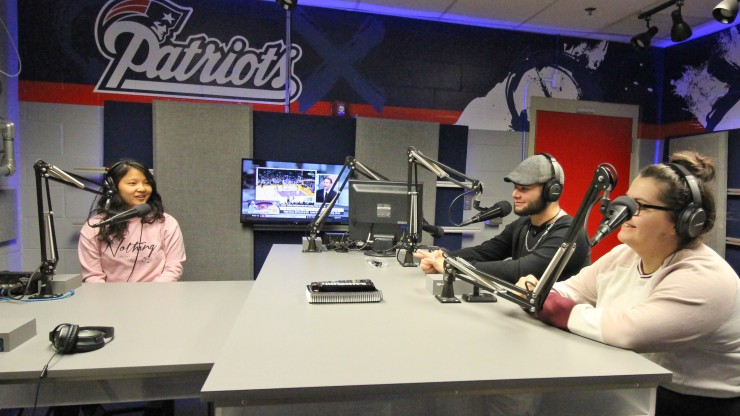 Three students wear headsets in front of microphones in the radio broadcasting stadium at Gillette Stadium.