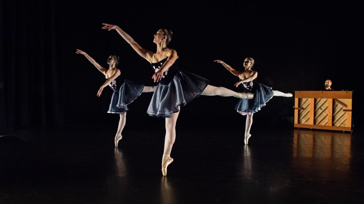 Three ballet students performing a dance on pointe while a pianist plays in the background.