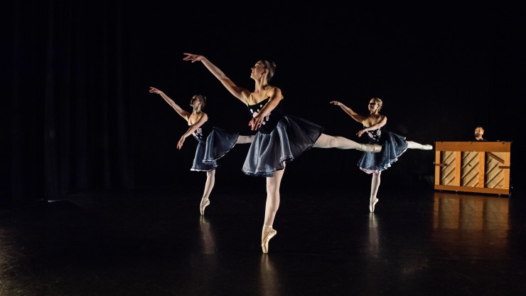 Three ballet students on their toes during a pointe dance onstage with a pianist playing in the background.