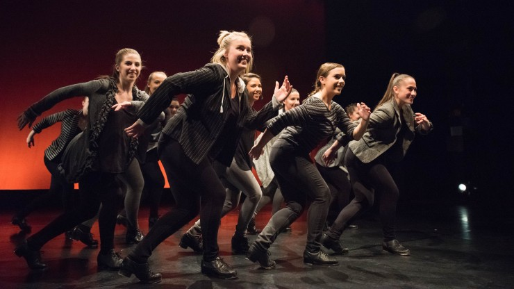 A group of dance students smiling while onstage during a tap dance performance.