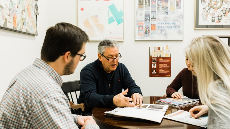 A professor sits with three students to explain the business programs.