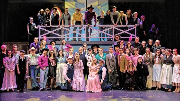 The entire cast of a theatre performance smiling while in costume onstage.