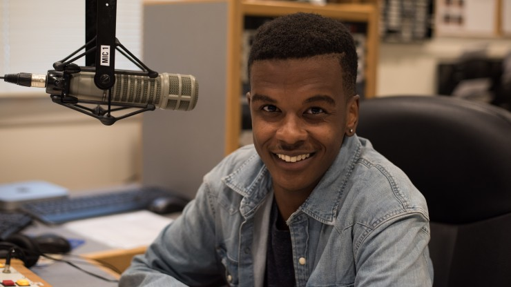 A student smiling at the camera in the Power88 radio station.