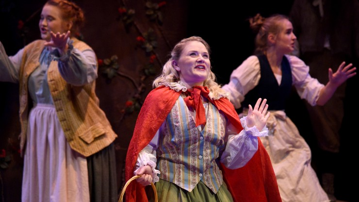 Multiple students singing during a scene from the Into The Woods performance.