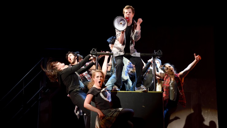 Students singing while hanging off a platform during the American Idiot performance.