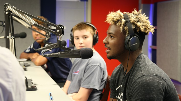 Students in the radio station at Gillette Stadium talking into the broadcasting microphones.