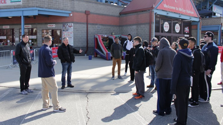 A group of students listen to a professor speak while outside of McCoy Stadium, home of the Pawtucket Red Sox.