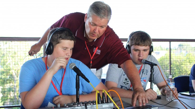 A professor helps students adjusting the soundboard while they are gaining hands-on experience as radio broadcasters.