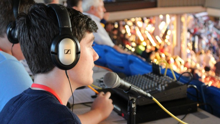 A student wearing headphones sits in front of a microphone while gaining experience as a sports broadcaster at McCoy Stadium during a Pawtucket Red Sox game.