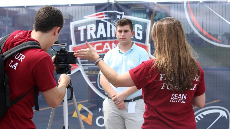 A student stands in front of a camera as two other people work the camera equipment while broadcasting from Patriots Training Camp at Gillette Stadium.
