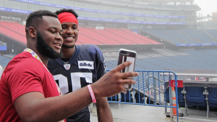A student takes a photo with a New England Patriots player while attending Patriots Training Camp at Gillette Stadium.