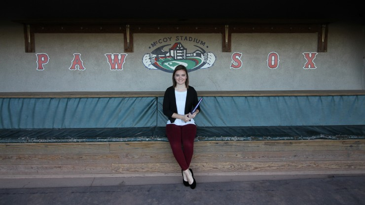 A student sitting in the dugout at McCoy Stadium, home of the Pawtucket Red Sox.