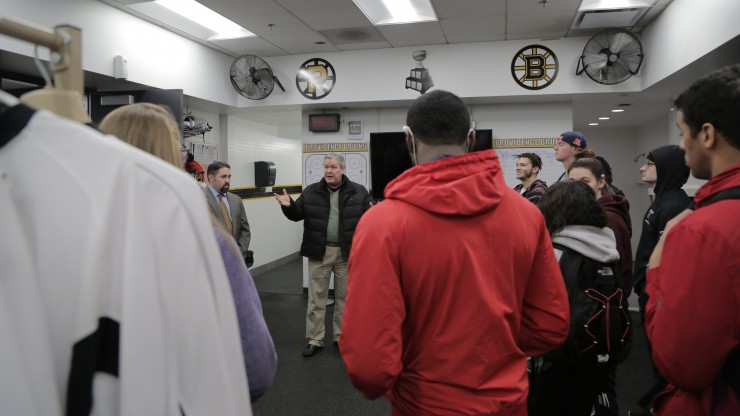 A professor speaks to a group of students in the Providence Bruins' locker room while on a tour of the Dunkin Donuts Center facilities.