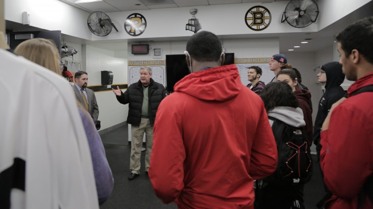 A professor speaks to a group of students while inside the Providence Bruins locker room during a tour of the Dunkin Donuts Center.