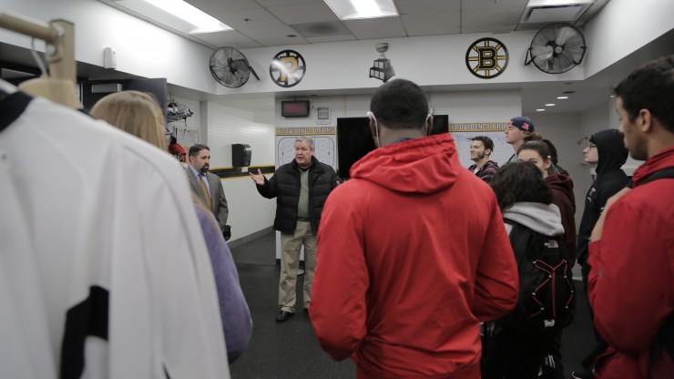 A professor speaking to a group of students inside the Providence Bruins lockerroom while on a tour of the facility.