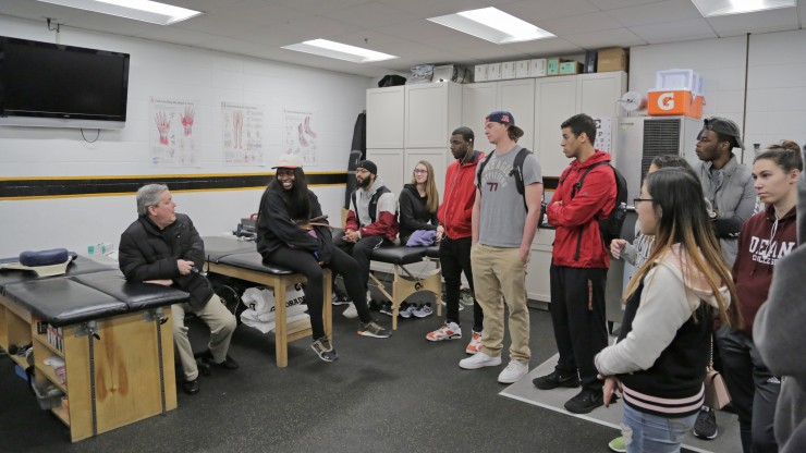 A professor explaining sports management to a group of students who are gathered around listening.