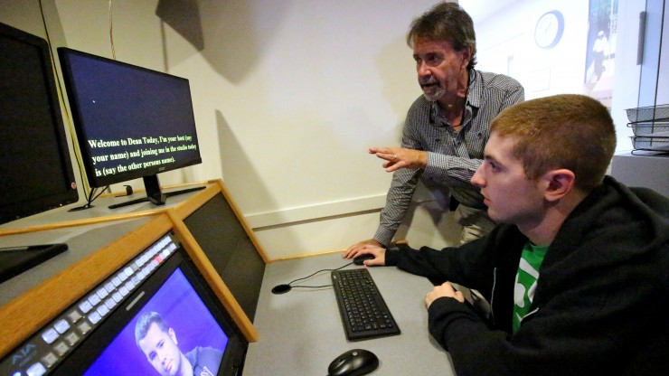 """Professor working with student behind the teleprompter on set of the news show """"Dean Today"""" in the Digital Media and Arts Center."""