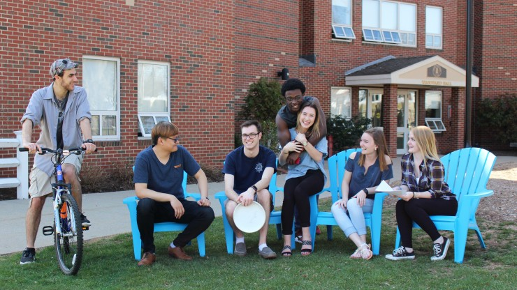 A group of students sitting outside and enjoying the weather in front of Woodward Hall.