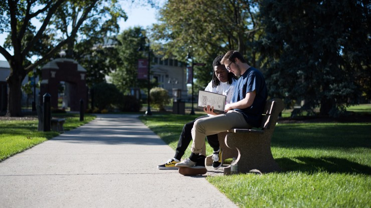 Students studying together on a bench outside of Awpie Way in front of Dean Hall.