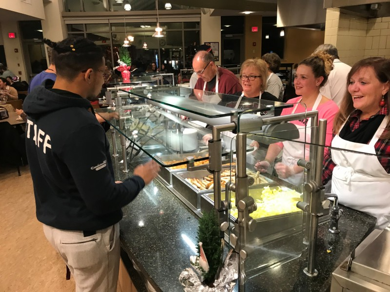 Image of a student being served breakfast food by faculty and staff at late night breakfast.