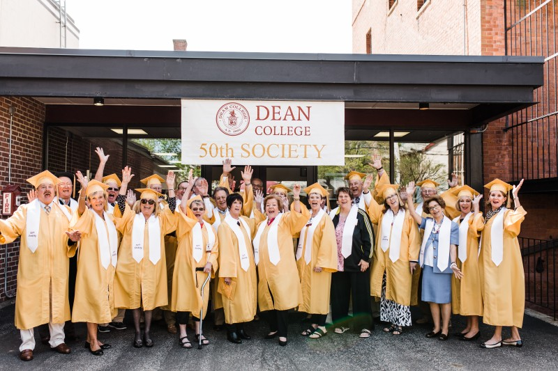 image of alumni from the 50th society wearing graduation caps and gowns smiling in front of the dean college 50th society sign.