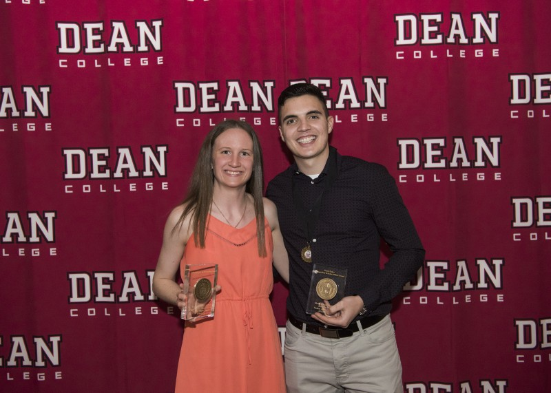Image of two students holding awards for athletic and academic achievement and standing in front of a dean college backdrop