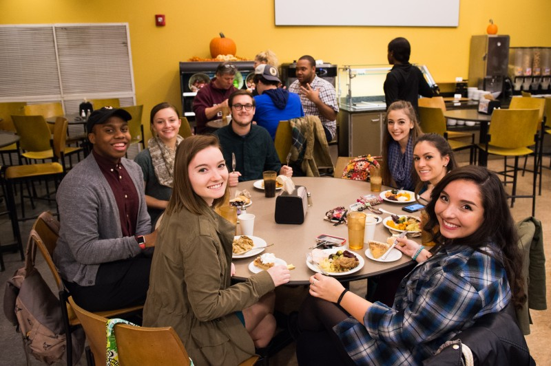 image of students sitting around a dinner table in the dining center smiling at the camera with their plates full of food from thanksgiving dinner.