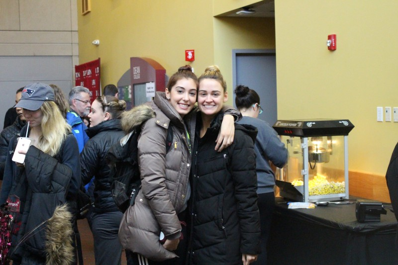 image of two students smiling and hugging in the dean college campus center to celebrate 50 days until commencement.