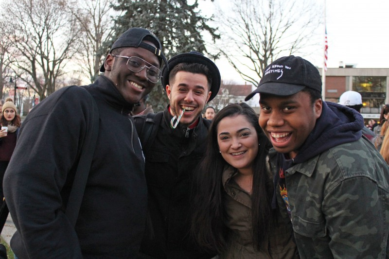 outdoor image of four students looking at the camera and smiling during an event for winter days.