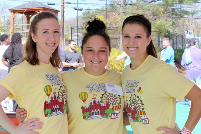 three students smiling while at the spring fling event on campus.