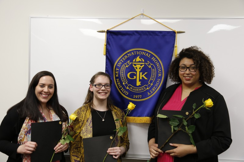image of three students standing in front of banner during Golden Key International Honor Society event.