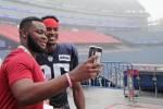 a student taking a photo with a new england patriots player at gillette stadium.